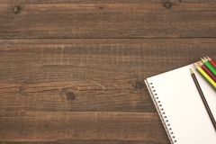 Öppnad spiral Notepad med den tomma sidan och många färgblyertspennor Royaltyfri Fotografi
