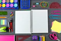 Öppnad tom anteckningsbok med ramen för skolatillförsel på den svart tavlan Royaltyfri Foto
