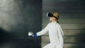 Práctica concentrada de la mujer del cercador que cerca ejercicios usando las auriculares de VR y que entrena al juego de la comp metrajes