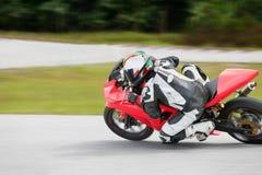 Práctica de la motocicleta que se inclina en una esquina rápida en pista Fotos de archivo