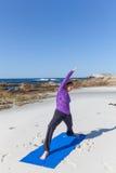 Práctica de la yoga en la playa Imagen de archivo libre de regalías