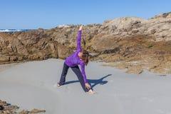 Práctica de la yoga en la playa Imagenes de archivo