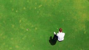 Prácticas del golfista profesional en un curso, poniendo una bola en un agujero almacen de metraje de vídeo