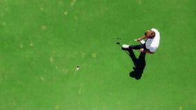 Prácticas jovenes del golfista en un curso, golpeando una bola en un agujero almacen de metraje de vídeo