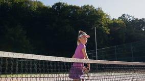Prática apta nova da mulher na batida com raquete e no salto durante o treinamento vídeos de arquivo