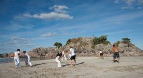 Prática Capoeira do grupo de pessoas na praia. imagem de stock royalty free