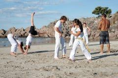 Prática Capoeira do grupo de pessoas na praia. foto de stock