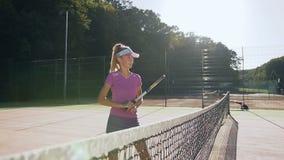 Prática da menina do esporte na batida usando uma raquete durante o treinamento filme