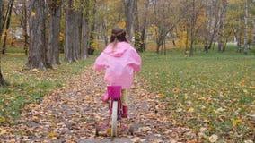 Prática da menina montar uma bicicleta cor-de-rosa no parque do outono filme