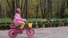 Prática da menina montar uma bicicleta cor-de-rosa no parque do outono video estoque