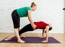 Prática de começo da ioga da senhora bonita nova com a classe privada do professor em casa, dando certo com o iogue fêmea profiss fotografia de stock