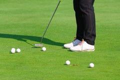 Prática do jogador de golfe que põe a bola de golfe sobre o golfe verde, nivelando o tempo imagem de stock royalty free