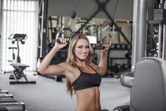 Prática 'sexy' loura do pulldown do halterofilista no gym Imagens de Stock Royalty Free