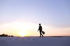 Prächtiger arabischer Kerl geht mit Gitarre in den Händen auf sandigem Hügel in DES lizenzfreie stockfotografie