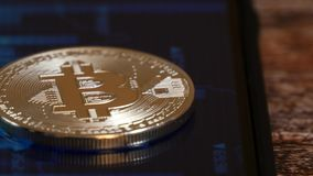 Prägen Sie das bitcoin und auf dem Schirm des Telefons mit einem Bild der Kurve von Zitate kriptovalyut liegen Handel in Schlüsse stock footage