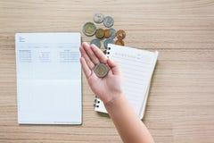 Prägen Sie in der Kinderhand mit Münzen und Bankkontobuchhintergrund Lizenzfreie Stockfotos
