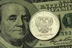 Prägen Sie in einem russischen Rubel auf einem Hintergrund des Amerikaners hundert Dollar Stockfotos