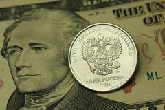 Prägen Sie in einem russischen Rubel gegen den Hintergrund des Amerikaners zehn Dollar Lizenzfreie Stockfotos