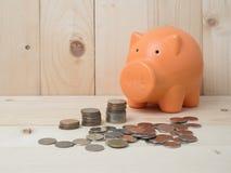Prägen Sie Stapel und Sparschwein für die Rettung mit Stapel von Münzen auf woodb Stockfotografie