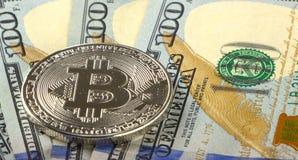 Prägt bitcoin auf einem Hintergrund von 100 amerikanischen Dollar Nahaufnahmen Lizenzfreie Stockfotos