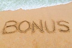 PRÄMIEN-Aufschrift geschrieben auf sandigen Strand mit dem Wellennähern Stockbilder