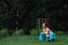 Pränatale Mutterschaft des schwangeren Yoga, die verschiedene Übungen tut im Park auf dem Gras, Atmung, dehnend, Statik aus Lizenzfreies Stockfoto
