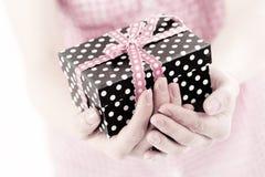 Präsentkarton in einem Frauenhandabschluß oben Lizenzfreie Stockfotos