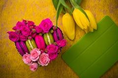 Präsentkartonherzform mit Blumentulpenmakronen und violettem Hintergrund der Tablette mit lov Lizenzfreie Stockbilder