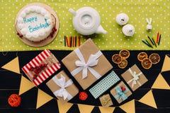 Präsentkartons und Geburtstagskuchen Stockbild