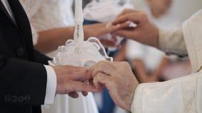 Präst som ber i kyrka på bröllopceremoni, och pålagda cirklar för nygifta personer arkivfilmer