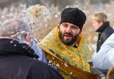 Prästen inviger mannen Arkivfoto