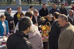 Prästen strilar dyrkare. Påsk. Royaltyfri Foto