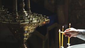Prästen tänder stearinljus och sätter på ljusstaken i katolsk tempel för kyrka inomhus lager videofilmer