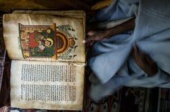 Prästen visar en forntida bok i Etiopien Arkivfoto