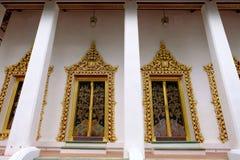 Prästvigningkorridor med guld- fönster av den kungliga templet i Nonthaburi royaltyfri bild