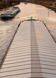 Pråmar som plying waterwayen, kanaliserar i industriellt område Arkivbild