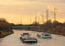 Pråmar som plying waterwayen, kanaliserar i industriellt område Royaltyfri Fotografi