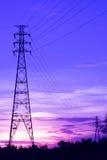 Près de et les tours à haute tension lointaines se sont reliées par des fils au coucher du soleil sous Violet Sky photographie stock