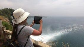 Près de la barrière en bois est une fille de touristes et prend des photos d'une belle cascade et de la mer bleue clips vidéos