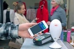 Près de la communication de champ - équipez accomplir des achats mobiles de femme de paiement photo stock