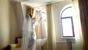 Près de la fenêtre, dans la chambre, robe l'épousant blanche accrochant sur les gouttières de fenêtre la jeune mariée, une belle  banque de vidéos