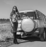 Près de la roue de secours la voiture est belle fille, noire et blanche Images stock