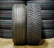 Près du nouveau pneu d'hiver avec les goujons et le pneu d'été image libre de droits