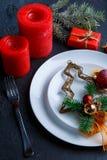 Près du plat avec un arbre de Noël décoratif sont les couverts, les bougies et un boîte-cadeau rouge avec un brin des arbres Photographie stock