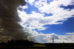 Près du village storm Le ciel rencontre un orage Le soleil brille par les nuages image libre de droits