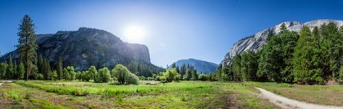 Pré et arbres entourés par les montagnes rocheuses Photo stock