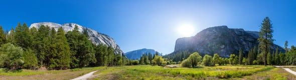 Pré et arbres entourés par les montagnes rocheuses Photographie stock libre de droits