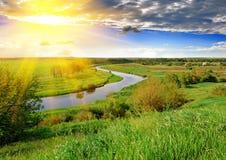 Pré et rivière de ressort le soir Image libre de droits