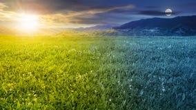 Pré frais d'herbe près des montagnes jour et nuit Photo libre de droits