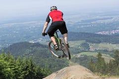 Précipice sautant de cavalier de vélo de montagne Photographie stock